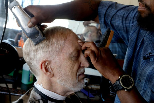 Detroit Free Press reporter Bill Laitner receives a hair cut by barber Terrez Taylor at Johnson & Co. Salon on Saturday, June 22, 2019. Laitner's wife, Eren Stephens who passed away in April of 2019, used to cut his hair in the bathroom of their Detroit home. After she passed away, Laitner hasn't wanted to get his hair cut by anyone else but decided recently to start going to this barbershop a couple blocks away on Jefferson Avenue.