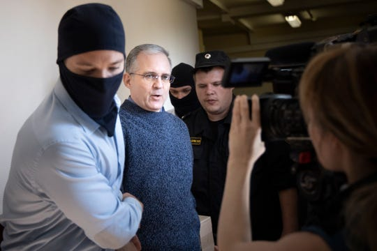 Paul Whelan, second from left, was arrested and accused of spying in Moscow. He speaks to a journalist as he escorted by Russian Federal Security Service officers into a courtroom in Moscow, Russia, Friday, Aug. 23, 2019.
