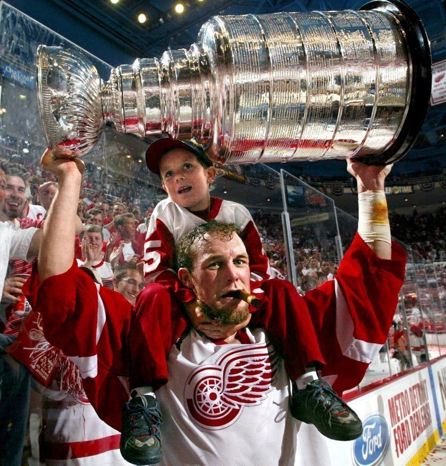 Darren McCarty with his then 5-year-old son, Griffin on his shoulders raises the Stanley Cup during post game celebrations after their Game 5 win over the Carolina Hurricanes in 2002.
