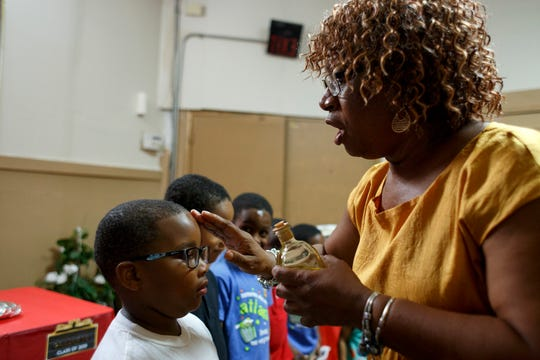 King of Kings Missionary Baptist Church minister, Sarah Johnson anoints and prays for Keith Steel, 6, during a scholarship and certificate reception on Saturday, Aug. 10, 2019 in Detroit. Minner Latham and her late husband, Gerald Latham, as well as others from their church made sure that each student from their congregation received a monetary gift for graduating on to the next grade as well as a scholarship to graduating high school seniors.