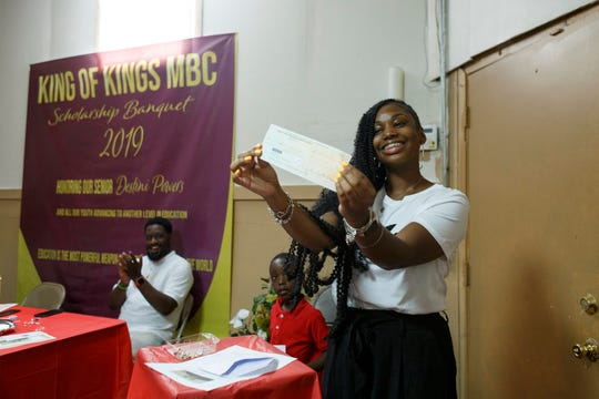 Destini Powers, 18, and a soon-to-be freshman at Western Michigan University, holds up her scholarship award at the King of Kings Missionary Baptist Church on Saturday, Aug. 10, 2019 in Detroit. Minner Latham and her late husband, Gerald Latham, as well as others from their church made sure that each student from their congregation received a monetary gift for graduating on to the next grade as well as a scholarship to graduating high school seniors.