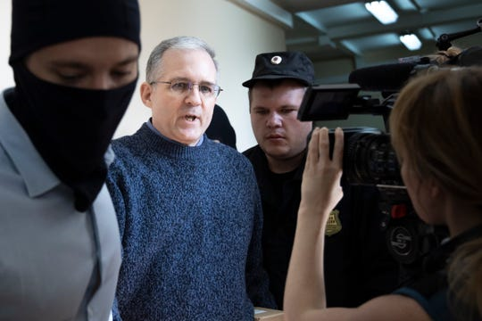 Paul Whelan, a former U.S. Marine, center, who was arrested for alleged spying in Moscow at the end of 2018, speaks to a journalist while being escorted for a hearing in a court room in Moscow, Russia, Friday, Aug. 23, 2019. (AP Photo/Alexander Zemlianichenko)
