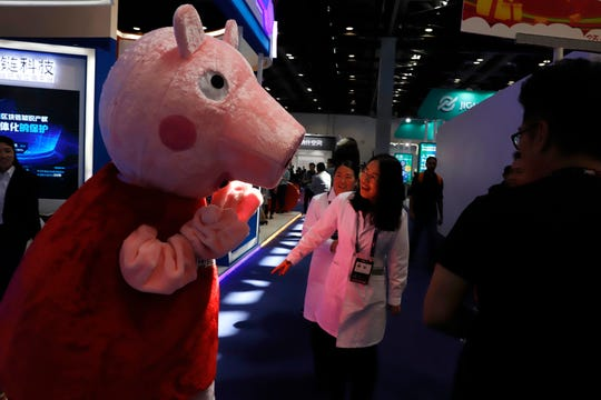 "A Peppa Pig mascot during the Global Mobile Internet Conference in Beijing, China, in 2018. Hasbro  will pay about $4 billion to buy Entertainment One Ltd, a British entertainment company that produces ""Peppa Pig,"" ""PJ Masks"" and other animated shows for preschoolers."