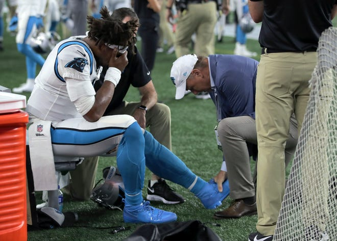 Panthers quarterback Cam Newton receives attention on the sideline after an injury in the first half of Thursday's preseason game.