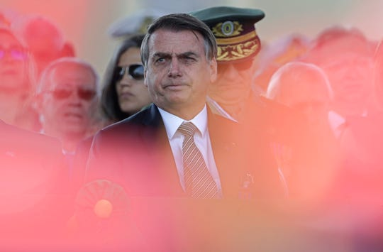 With the red plumes of the helmets of the honor guard in the foreground, wldBrazils President Jair Bolsonaro attends during a military ceremony for the Day of the Soldier, at Army Headquarters in Brasilia, Brazil, Friday, Aug. 23, 2019.