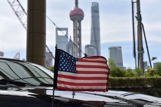 A U.S. flag flies on a American consulate car in China. China on Friday retaliated with tariffs that will hit producers of cars in the U.S.