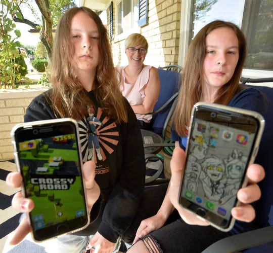 Elizabeth Momper of Southfield, left, and her identical twin Emily, 12, show off their favorite game apps as their mother, Kitrina Momper, talks about her daughters getting cellphones for the first time recently. They will not be able to use their cellphones at Anderson Middle School in Berkley this year.