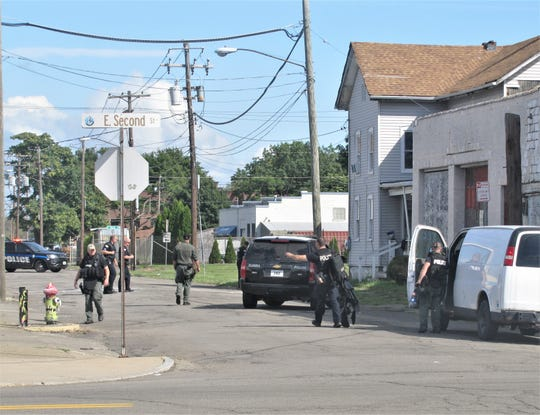 Law enforcement personnel search for evidence after taking one person into custody following a shots-fired report early Friday near the intersection of Baldwin and East Second streets in Elmira.