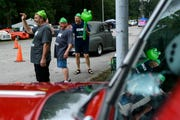 James Bays, front to back, Rick Marvin and Al Seidel of Indianapolis, Ind., ask street rod drivers to honk their horns and smile as they pull into the Vanderburgh 4-H Center to find a parking spot during the first morning of the 45th annual Frog Follies show in Evansville, Ind., Friday, Aug. 23, 2019. The group arrived at the fairgrounds before 3 a.m. to secure parking spots right beside the main gate.