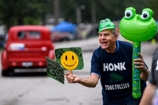 "Al Seidel of Indianapolis, Ind., asks street rod drivers to honk their horns and smile as they pull into the Vanderburgh 4-H Center during the first morning of the 45th annual Frog Follies show in Evansville, Ind., Friday, Aug. 23, 2019. ""I am here to have fun and enjoy the cars [which made me] wonder why so many people were frowning as they were coming into the show,"" Seidel said, when asked why he has been greeting drivers at the gate for the past 10 years."
