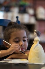 Melania Martinez, 5, of Alva, works on a ceramic princess at The Paint Escape in Cape Coral.