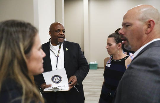 Department of Workforce Development employees Cindy Holzman, left, Thomas R. Beverly, middle, Jolene Wilkens and Derek Jablonicky talk amongst themselves during the job fair for Veterans on Thursday, Aug. 22, 2019, located at 7001 Gass Lake Rd in Manitowoc, Wis. Ebony Cox/USA TODAY NETWORK-Wisconsin