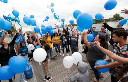 Family and friends of Federico Abarca Jr., a Preble High School student who was shot and killed during an attempted drug robbery, release balloons into the sky to honor the six-month anniversary of his death during a brief ceremony Aug. 22, 2019, on CityDeck in Green Bay, Wis.