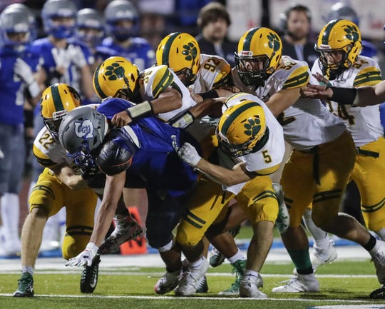 Ashwaubenon's Mitchell Opperman (22), Zain Ruffin (36) and Connor Ramage (5) bring down Southwest's running back Taejon Richard (8) on Thursday night.