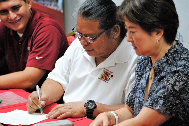 In this file photo from earlier this year, Frank Florig, president and CEO of Special Olympics Guam, signs a memorandum of understanding with Sandra Low, at right. Low is the president of the Guam National Badminton Federation. The two groups announced a partnership on Aug. 23, 2019 at Wyndham Garden Guam.