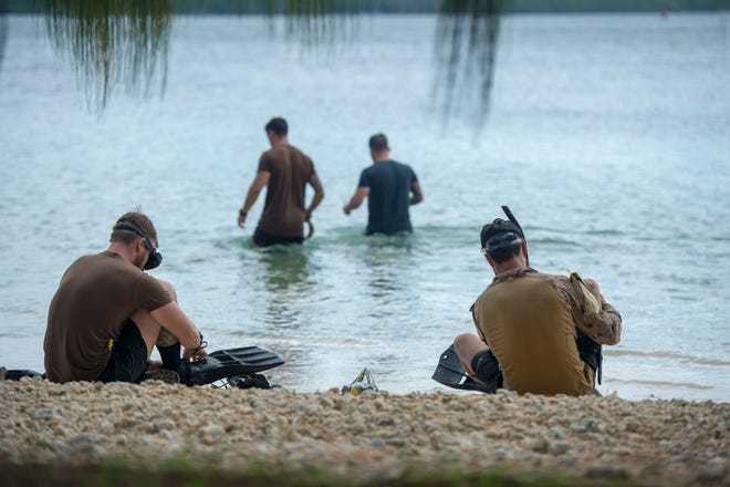 Clearance divers assigned to the Royal Canadian Navy's Fleet Diving Unit Pacific enter the water to search for simulated underwater mines during a subject matter knowledge exchange as part of Exercise HYDRACRAB. The exercise is conducted by forces from Australia, Canada, New Zealand, and the United States to prepare the participating Explosive Ordnance Disposal forces to operate together.