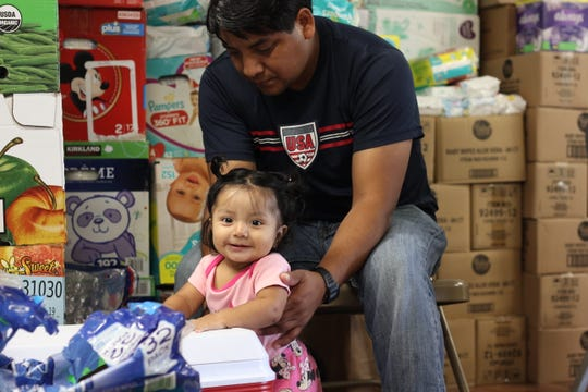 Romeo Ramirez holds his 9-month-old daughter, Elizabeth, on Aug. 22, 2019. After his wife was arrested during an immigration raid on Aug. 7, 2019, Ramirez has been taking care of the couple's four children alone. The baby was breastfeeding before she was separated from her mother, Ramirez said.