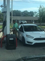 This image from Paul Russell Reed's Facebook post shows Derek Clark paying for a woman's gas after he pushed her car with an empty gas tank to the pump.