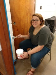 Meg Kiestler touches up the paint in preparation for a power paint sprayer during a cleanup of the Karns Youth Center. 8/17/19