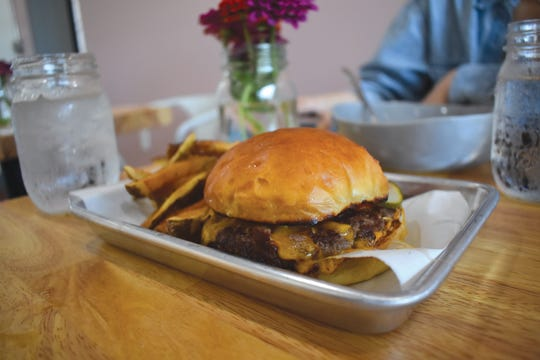 Made with a blend of beef and pork for maximum tenderness, Simpl's house burger is a standout. Here, it's served with cheese, pickled, tomato, and aioli atop a Paysan bun.