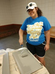 Project manager Lexie Austin paints the kitchen cabinets a shade of gray with warm brown undertones to match the new countertops at a cleanup of the Karns Youth Center. 8/2019
