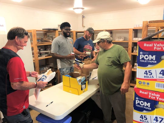Clockwise from left, Steve Randolph, Chris Comeaux, Jim Willoughby and Alvin Anderson from Agape assist in packing food bags for FISH on Aug. 23 in the Church of the Good Shepherd.