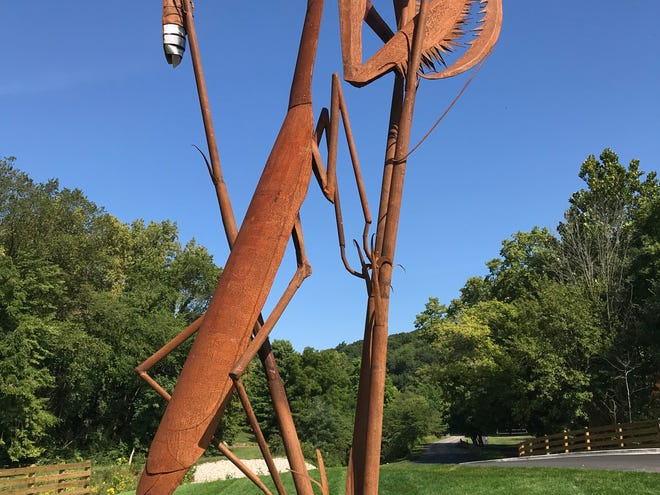 """""""Harmony Afield,"""" a 26-foot sculpture of a praying mantis and three fireflies, was installed this week at the entrance to West Lafayette's Happy Hollow Park. The piece, by Butler, Pennsylvania, artist Bill Secunda, is one of four recently installed at entrances to the West Lafayette park."""