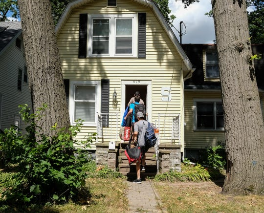 Students move their belongings into a house on Ann Street in East Lansing Friday, Aug. 23, 2019. From front to back, AJ Batshon from Novi, Connor Moesta from Lake Orion and Nick Strom from Novi. They rented the house along with one other person through a rental agency.