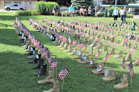 Volunteers set up almost 400 boots from families ofthe fallenin Wisconsin in Two Rivers' Central Park to mark the Walk for the Fallen.