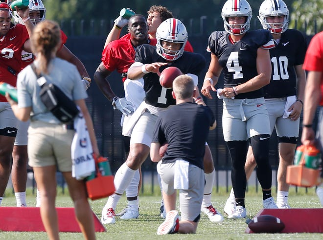 Ohio State quarterback Justin Fields takes a snap during training camp drills.