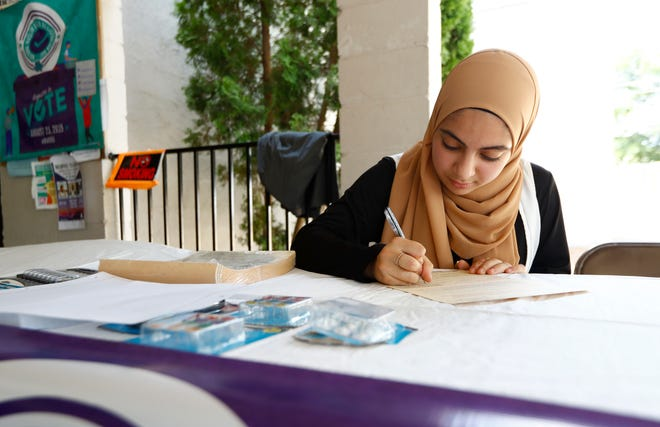 Haneen Jaber, who will turn 18 this October, fills out a voter registration form during an event run as a part of National Muslim Voter Registration Day on Aug. 23.
