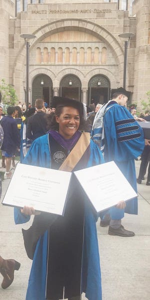 Bianca Smith poses with her Masters in business and law degree from Case Western in Ohio. Now the assistant AD at Carroll, her goal is to coach baseball.
