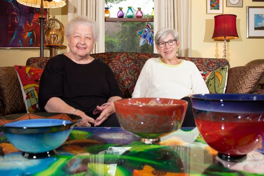 Barbara Muth, left, and Mary Bock, who have both been involved in the Starving Artists' Show at Mount Mary University since its founding a half-century ago, take a moment in Muth's house in Germantown. In the foreground are some of the pieces Muth has bought at the show over the years.