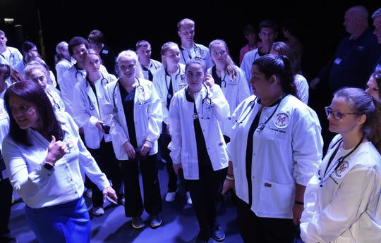 Mountain Home seniors participating in an internship program with Baxter Regional Medical Center gather onstage after being presented with a white coat, stethoscope and blood pressure cuff on Friday.