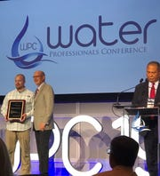 Milcrofton Utility District General Manager Mike Jones accepts the AWWA Award of Excellence.