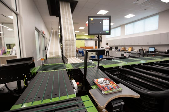 The new Lee County Public Library uses an automated library sorter on Friday, Aug. 23, 2019, in Bonita Springs. The new tool will staff time and get books back on shelves sooner.