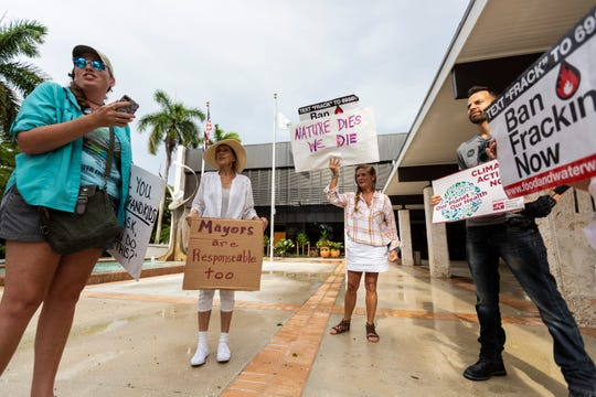 From left to right, Colleen Gill, Drucilla Neeley, Wanda Klopf and Brian Terenna protest in front of Naples City Hall on Friday, Aug. 23, 2019. They paraded through downtown Naples later in an effort to bring attention to climate change.
