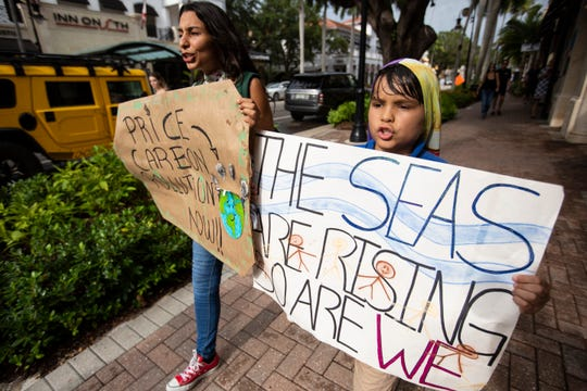 Solemi Hernandez, left, and Patrick Maguire, 8, right, parade through downtown Naples in an effort to bring attention to climate change on Friday, Aug. 23, 2019.