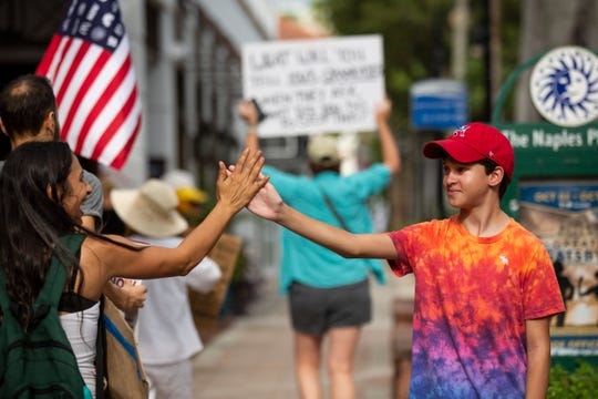 Rocco Affronti, 11, right, gives Solemi Hernandez, left, a high-five during a protest on Friday, Aug. 23, 2019, in downtown Naples. A small group protesters paraded through downtown Naples in an effort to bring attention to climate change.