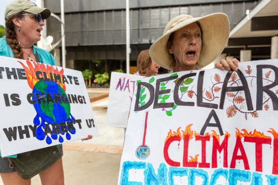 Drucilla Neeley, right, and Colleen Gill, left, protest in front of Naples City Hall on Friday, Aug. 23, 2019. They paraded through downtown Naples later in an effort to bring attention to climate change.