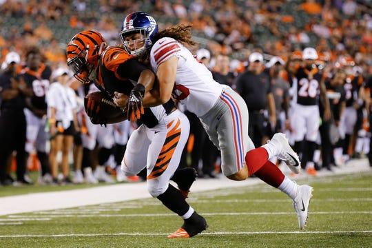 Cincinnati Bengals wide receiver Hunter Sharp, left, is tackled by New York Giants linebacker Josiah Tauaefa during the second half of an NFL preseason football game Thursday, Aug. 22, 2019, in Cincinnati.
