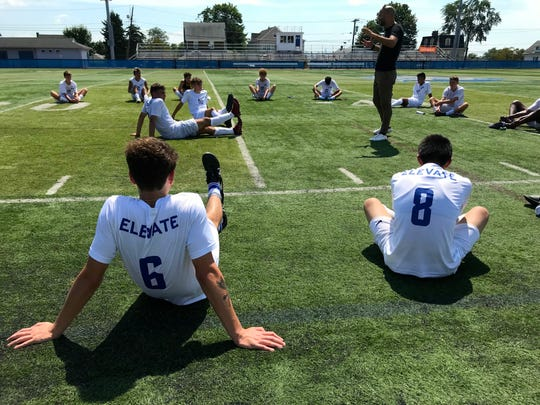 Coach Alberico De Pierro chats with the Blue Devils after their scrimmage against Bergenfield. Nate Auslander (6) and Jefferson Gonzalez (8) stretch in the sun.