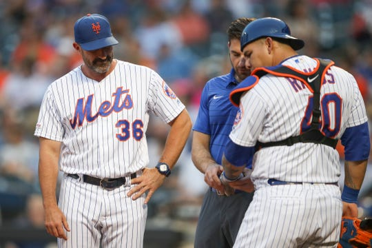New York Mets manager Mickey Callaway (36) watches as a trainer checks on catcher Wilson Ramos' hand during the first inning of the team's baseball game against the Cleveland Indians, Thursday, Aug. 22, 2019, in New York. (AP Photo/Mary Altaffer)