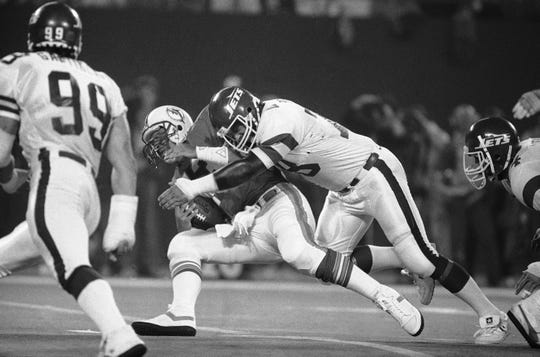 Miami Dolphins quarterback Dan Marino, left, can't get away from the clutches of the New York Jets Barry Bennett as he's sacked for a loss in the first quarter, Oct. 14, 1985 at Giants Stadium in East Rutherford, N.J. (AP Photo/Ray Stubblebine)