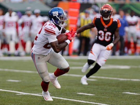 Aug 22, 2019; Cincinnati, OH, USA; New York Giants running back Wayne Gallman (22) runs for yardage against Cincinnati Bengals free safety Jessie Bates (30) during the first half at Paul Brown Stadium.