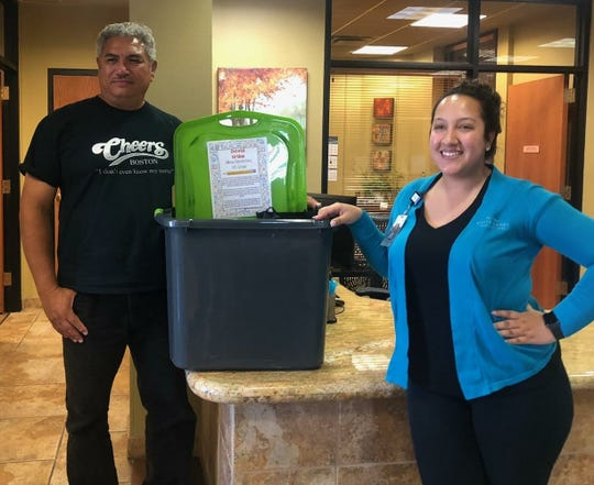 Hillrise Elementary school teacher David Uribe accepts his school supply basket from White Sands FCU employee Amanda Montoya.
