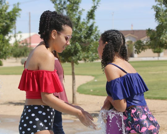Julia Huebert, 13 , and Kaitlin Huebert 12, play at the Metro Verde Splash Pad park Friday Aug. 23, 2019. The sisters attend Pecos Connections Academy, a tuition free online school.