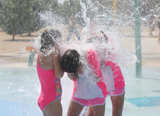 """Twins Sarette and Maya Patrick, 12, and a friend, hide their faces as they get """"splashed,"""" during a school picnic at Metro Verde Splash park in Las Cruces. The twins attend an online public charter school called Pecos Connections Academy."""