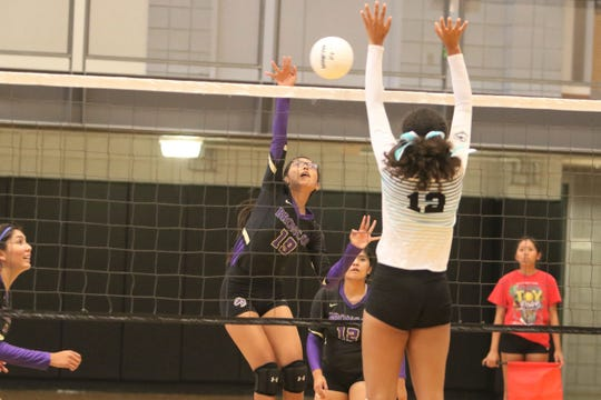 Kirtland Central's Tatyana Benally hits the ball for a kill against Navajo Prep's Akua Carr during Thursday's volleyball match at the Eagles Nest in Farmington.