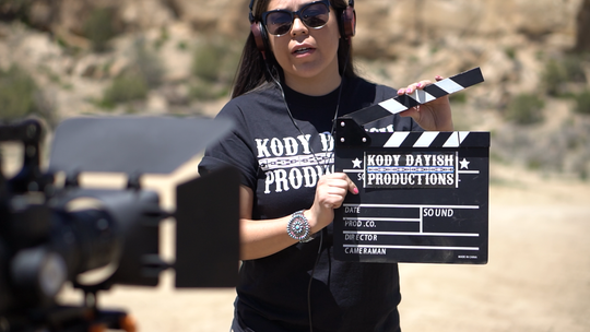 "Kolette Dayish holds a slate during the shooting of the film ""Parole."""